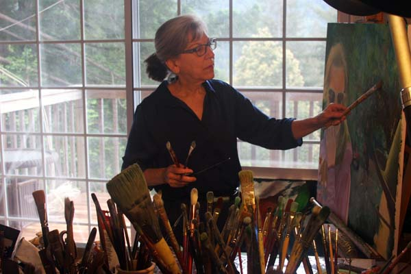 artist in studio with brushes easel paintings large window view of mountains